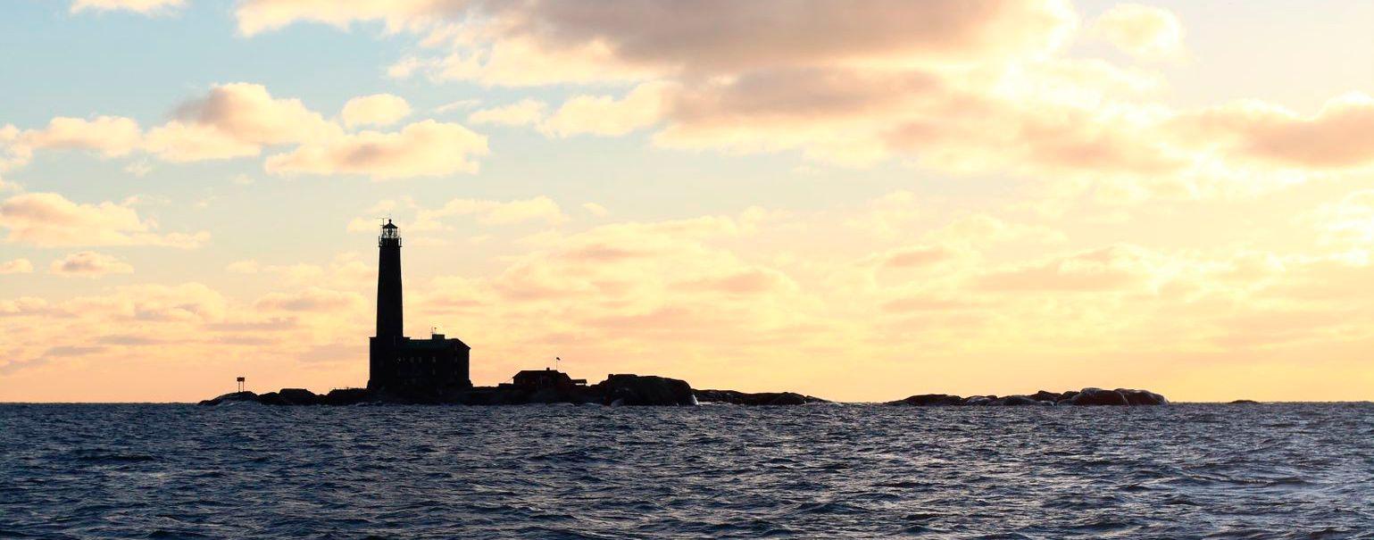 The shadow outline of Bengtskär Lighthouse against a setting sun.